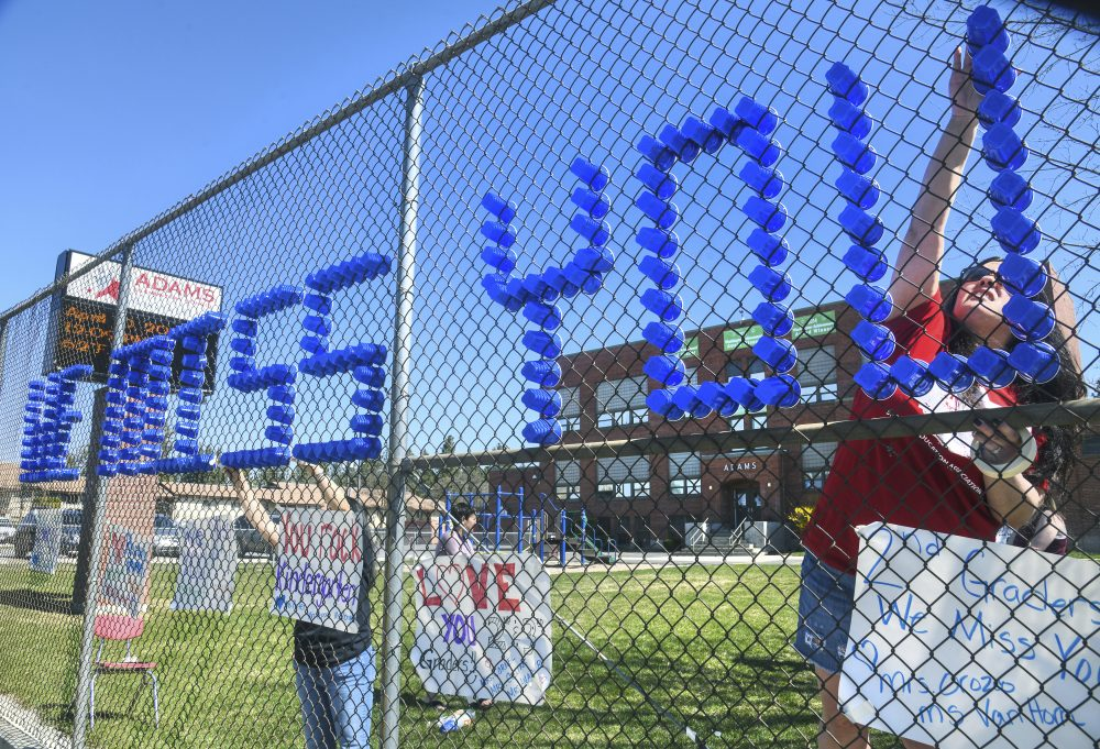 "Adams Elementary School third-grade teacher Lisel Corneil, left, and fifth-grade teacher Allie Campbell are among educators who constructed from plastic drinking cups a ""We Miss You All-Stars"" message to their students in a fence in Spokane, Wash."