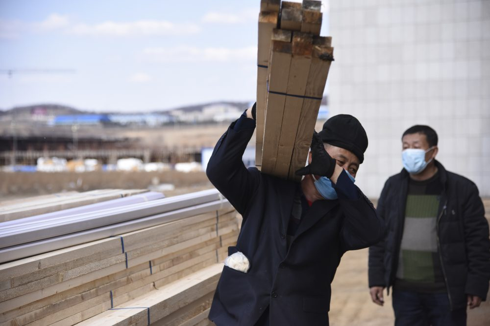 Laborers haul supplies to an office building being converted into a temporary hospital in Suifenhe in northeastern China's Heilongjiang Province on Friday. China is facing a new coronavirus flare-up along its remote northern border with Russia, far from the epicenter of Wuhan.