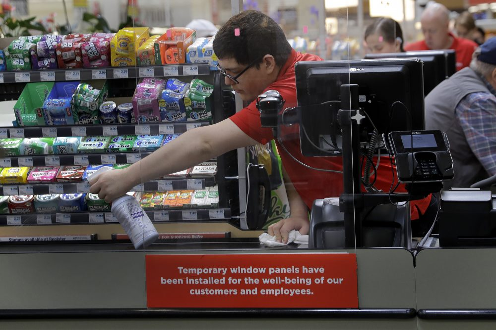Garrett Ward sprays disinfectant on a conveyor belt between checking out shoppers behind a plexiglass panel March 26 at a Hy-Vee grocery store in Overland Park, Kan.
