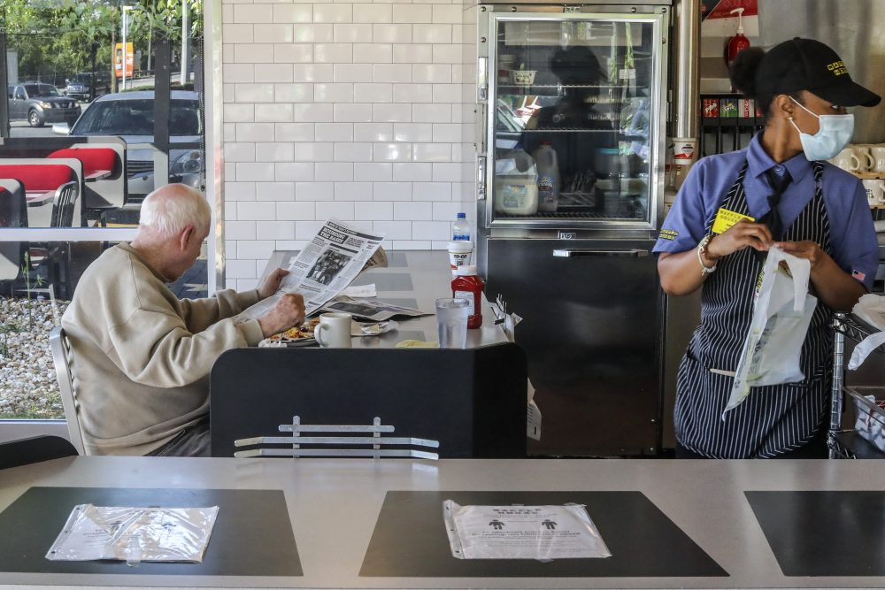 A Waffle House employee gets to-go orders ready as a seated guest eats his meal on April 27 in Brookhaven, Ga. Restaurants around metro Atlanta began to reopen dining rooms as restrictions were lifted.