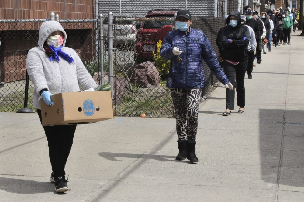 A woman carries a box of food away as hundreds others impacted by the COVID-19 virus outbreak wait in line at a Salvation Army center in Chelsea, Mass., on Wednesday.