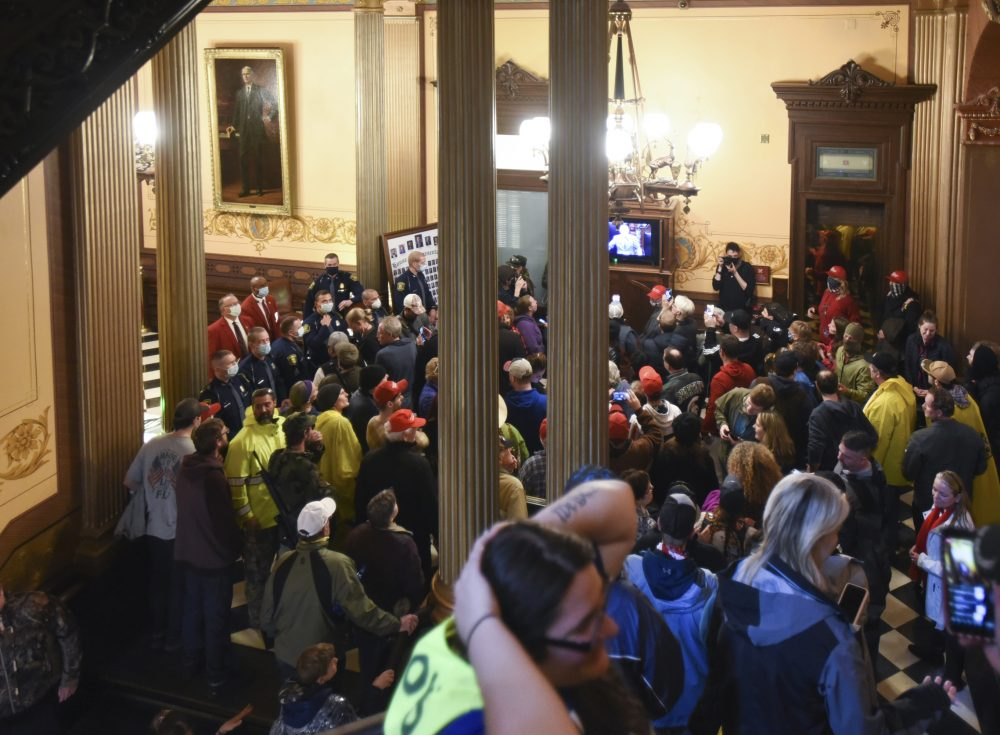 Protesters gather outside the entrance of the Michigan House of Representatives in Lansing, Mich. on Thursday.