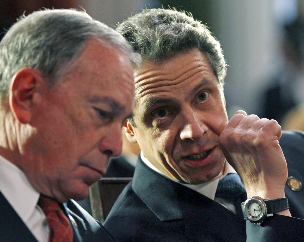 "Then-New York Mayor Michael Bloomberg, left, and New York Gov. Andrew Cuomo on March 16, 2012, at the Capitol, in Albany, N.Y.  Bloomberg will help create a ""tracing army"" that will help find people infected with the coronavirus and get them into isolation, Cuomo announced Wednesday."