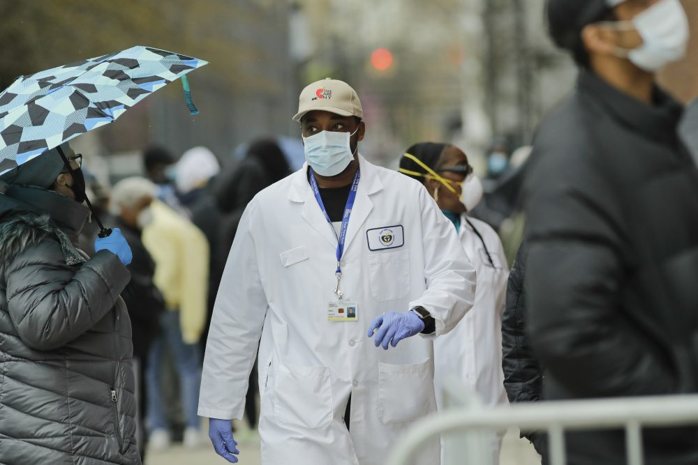 A medical worker walks past people lined up at Gotham Health East New York, a COVID-19 testing center, on Thursday in the Brooklyn borough of New York.