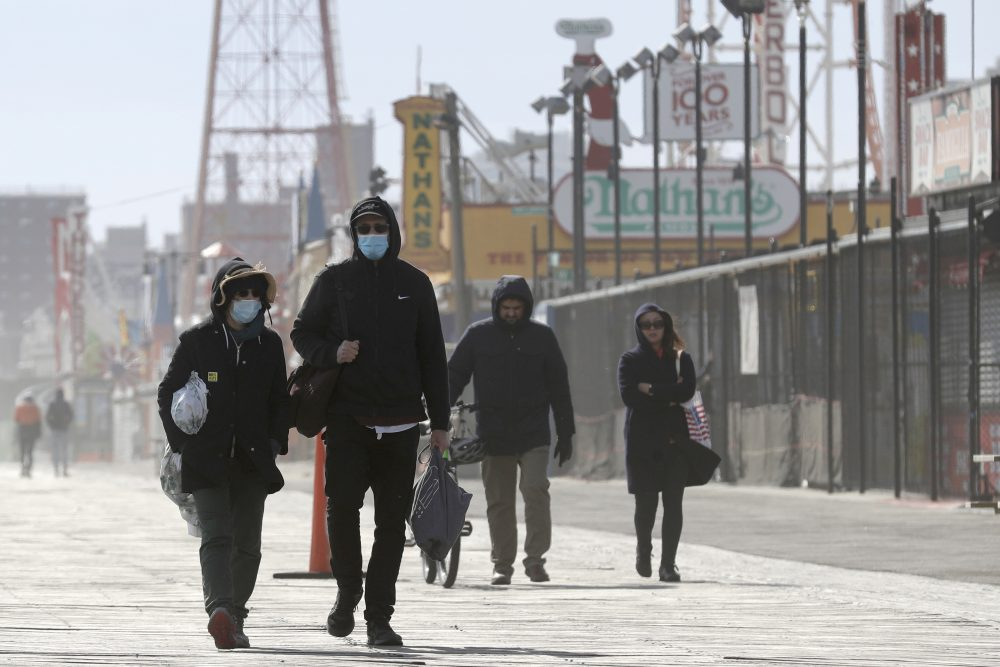 Pedestrians enjoy the warm weather on the boardwalk at Coney Island in New York, Sunday, April 12. Amid some signs of hope that the coronavirus infection rate is plateauing, New York is still wrapping up its worst week in deaths so far since the outbreak began.