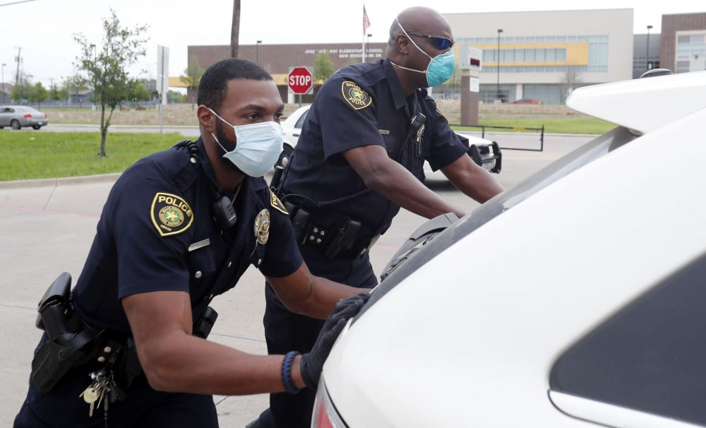 Dallas police officers push a car that ran out of gas while waiting in line for the weekly school meal pick up for students in Dallas.