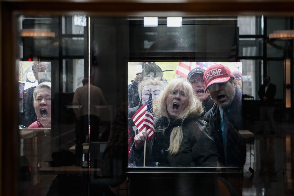 """Ohio state senate candidate Melissa Ackison, left, and other protesters shout outside the Statehouse Atrium, where reporters listen during the state of Ohio's coronavirus response update at the Ohio Statehouse in Columbus, Ohio, on Monday. The unprecedented national effort to shut down much of daily life to slow the spread of COVID-19 is prompting a growing number of protests. Ackison brought her 10-year-old son to the protest and said she has """"no fear whatsoever"""" of contracting the new coronavirus, dismissing it as """"hype."""""""