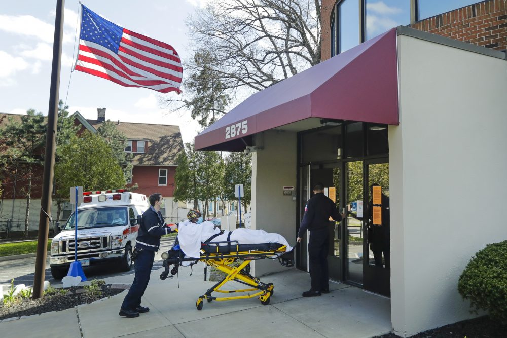 Medical workers bring a patient to the Northbridge Health Care Center Wednesday in Bridgeport, Conn. To slow the spread of the coronavirus inside nursing homes, Connecticut has begun transferring infected residents to off-site recovery centers following their release from hospitals.