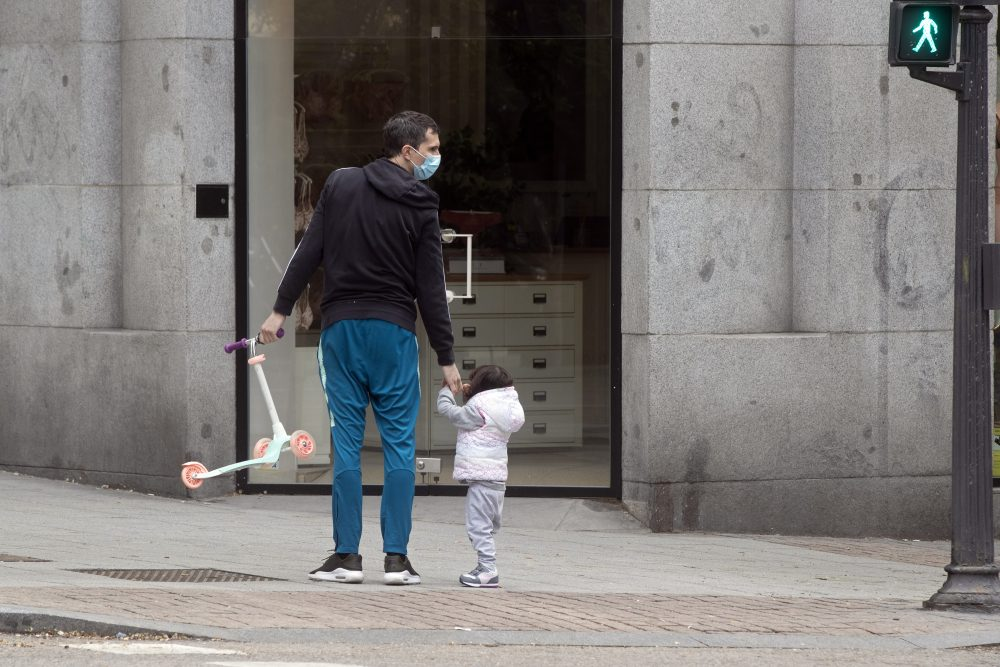 A man takes a young girl for a walk in Madrid, Spain, on Sunday. Children under 14 years old are finally allowed to take walks with a parent, ending six weeks of compete seclusion due to the coronavirus outbreak.