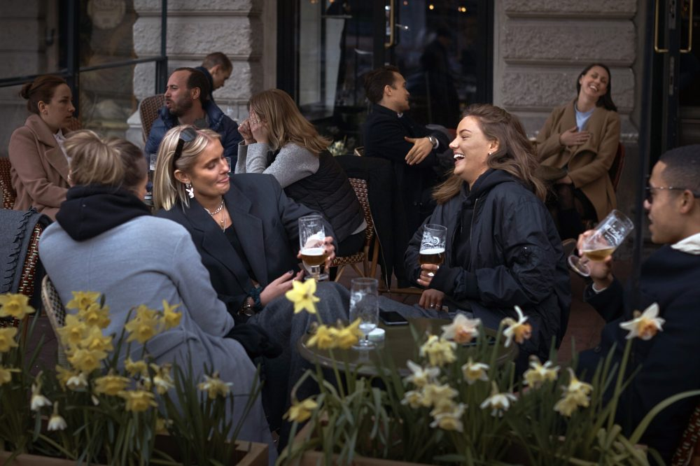 People chat and drink outside a bar on Wednesday in Stockholm, Sweden. Sweden is pursuing relatively liberal policies to fight the pandemic, even though there has been a sharp spike in deaths. Most restaurants and businesses are still open.