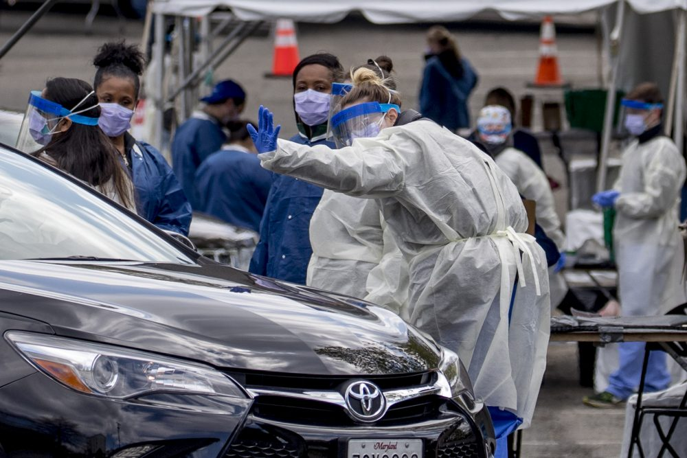 A medical worker waves goodbye after testing a young person for COVID-19 at a Children's National Hospital drive-through (drive-in) coronavirus testing site at Trinity University, Thursday, April 16 in Washington.