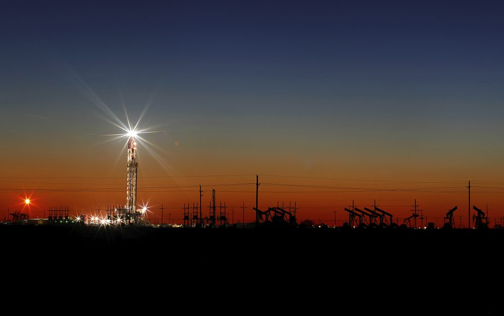 An oil rig lights up the horizon on the outskirts of Midland, Texas, on Thursday after a late sunset.