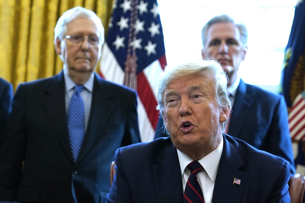 President Trump signs a stimulus package last month. Looking on are Senate Majority Leader Mitch McConnell, R-Ky., left, and House Minority Leader Kevin McCarthy of Calif.