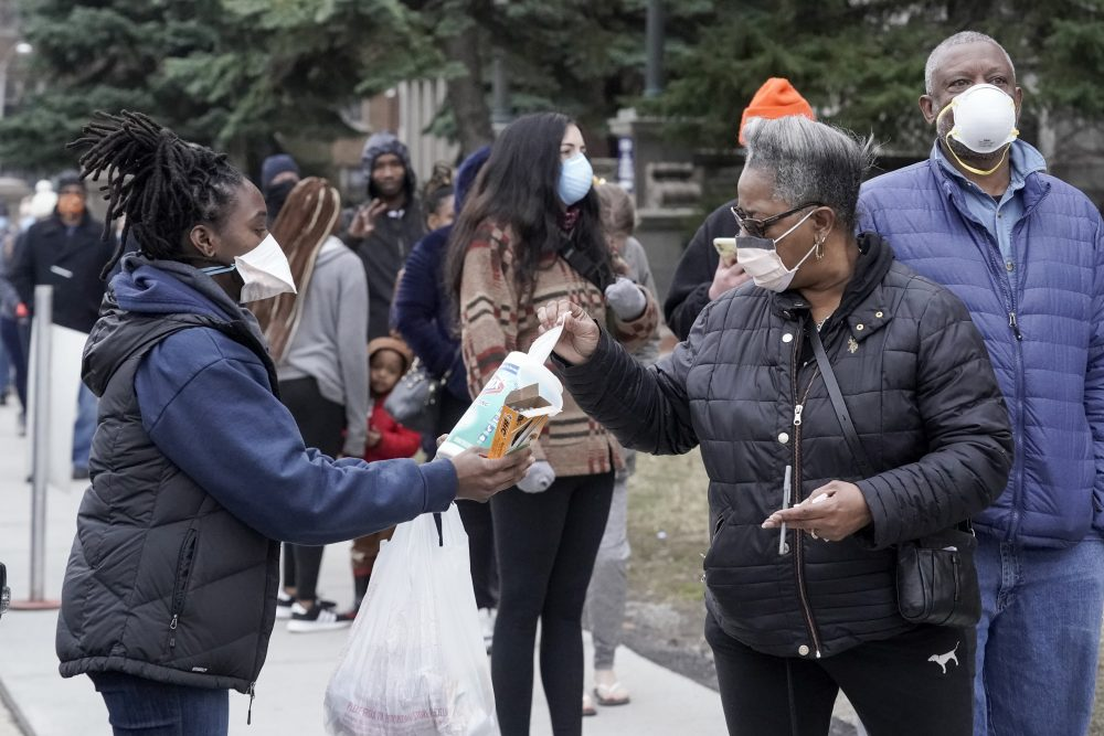 A worker hands out disinfectant wipes and pens as voters line up outside Riverside High School for Wisconsin's primary election Tuesday in Milwaukee.