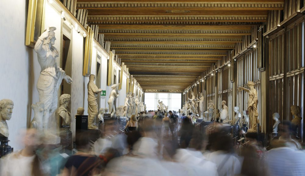 In this Aug. 6, 2019 file photo, visitors walk through corridors of the Uffizi Gallery Museum, in Florence, Italy.