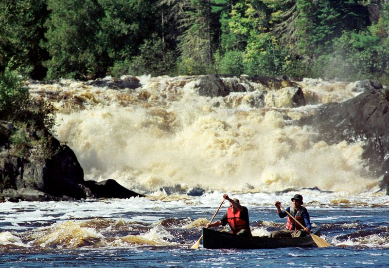Canoeists Jason Chamberlain, left, and Andrew Martin, both of Fort Kent, Maine, paddle through whitewater after portaging the 40-foot Allagash Falls, background in 1999 on the Allagash Wilderness Waterway