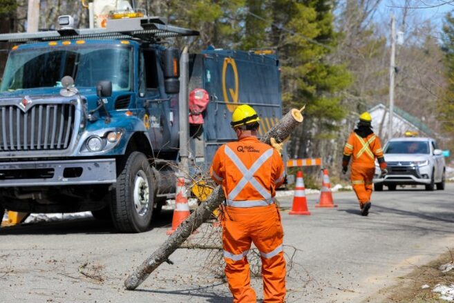 A repair crew sent to Maine by Hydro-Quebec works to restore power near Belfast on Sunday.