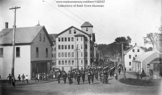 A parade crosses the bridge that spanned the Mousam River going south on Main Street in Kennebunk in this circa 1900 photo.  The Davis Shoe Company stands as the tallest building to the left. On May 3, 1903 there was a large fire in the Davis Shoe Company building which destroyed most of the buildings in this photograph, with others nearby suffering heavy damage.
