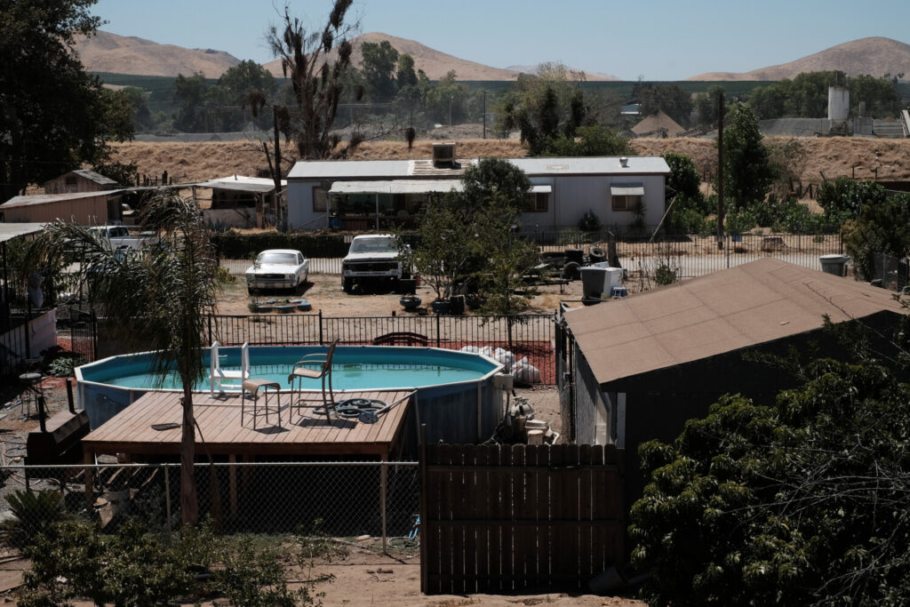 A swimming pool contrasts with the drought dried landscape in East Porterville, Calif., in 2015. With access to water limited, the pool's owner doesn't drain it, instead using chemicals to keep it clean.