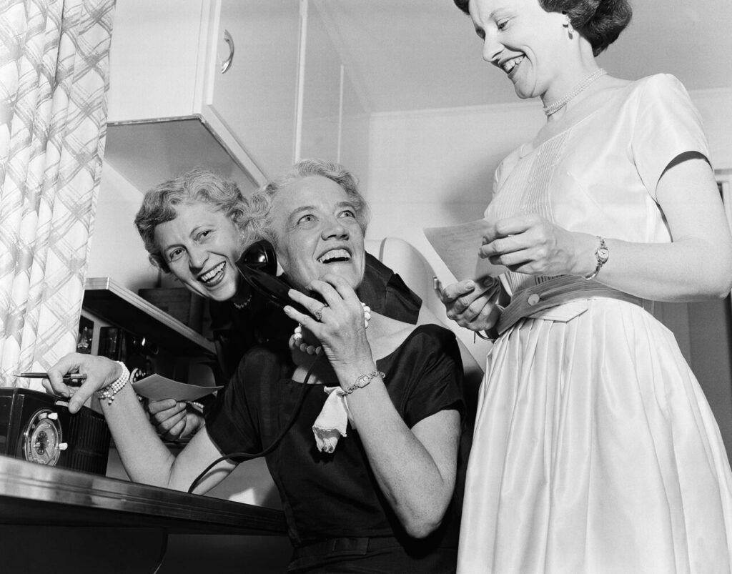 Sen. Margaret Chase Smith looks up to call out good news to friends in the kitchen of her home in Skowhegan on June 21, 1954, as returns of the primary gave her a wide lead for the Republican senatorial nomination. On her left is Blanche Hudon and on her right is Helen Wing.