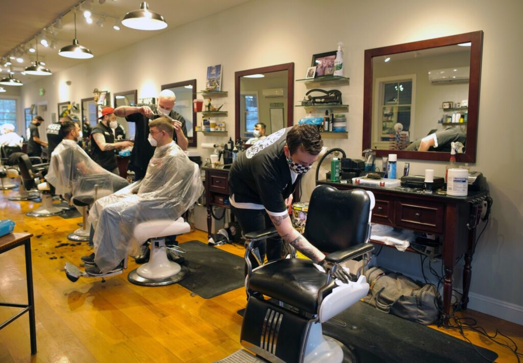 Garrison Guay sanitizes his barber chair in between customers at the Main Street Barber Shop in Kennebunk, which reopened Friday morning. The shop took customers by appointment only, under guidelines issued by the state. The barbers were booked for the whole day.