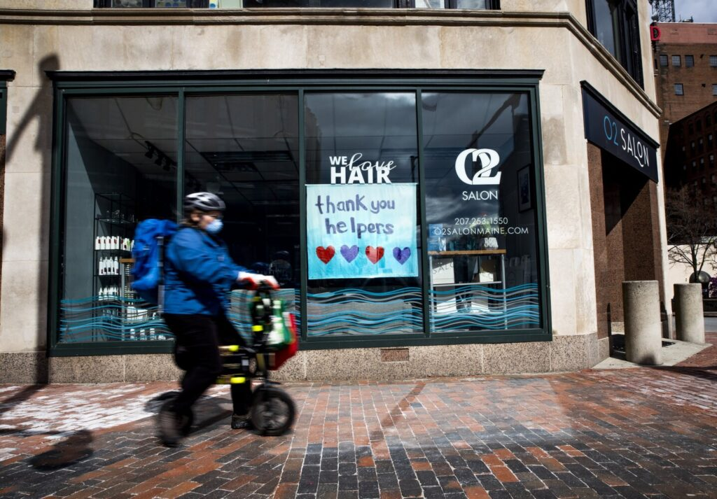 A pedestrian passes a sign in the window of a closed salon on Congress Street in Portland on Monday morning.