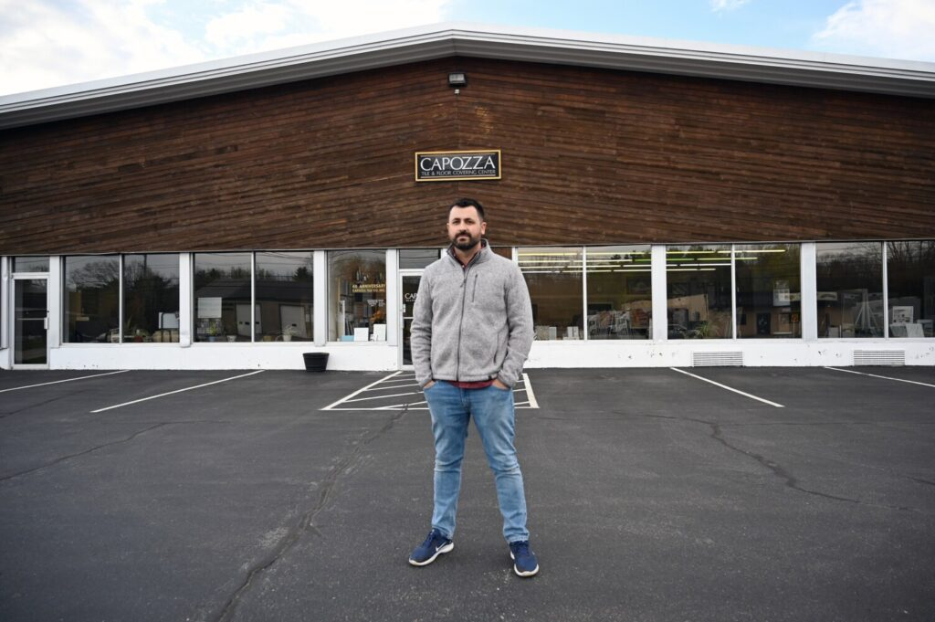 Joe Capozza of Capozza Tile and Flooring Center in Portland stands in front of his business Wednesday. Capozza has used the federal Paycheck Protection Program to help his business. Others have opted out because they believe the terms wold not work for them.