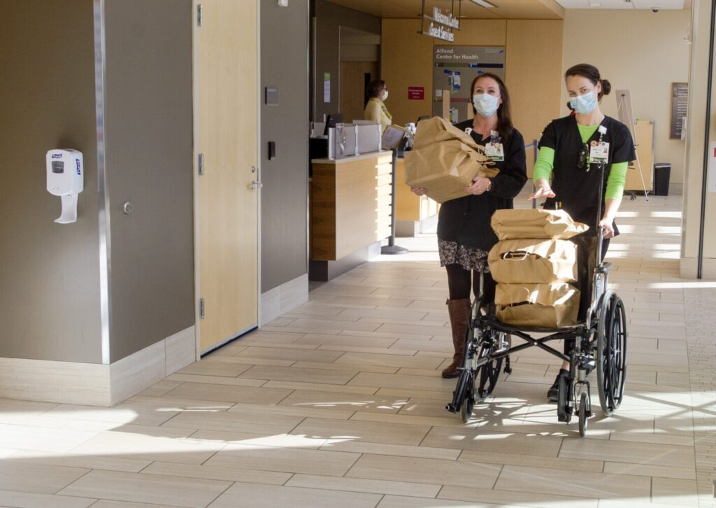 Nurses Danielle Easler, left and Emily Knox take dinners that were bought from the Quarry Tap Room with donations to a GoFundMe campaign to 1 West floor Thursday at MaineGeneral in Augusta.