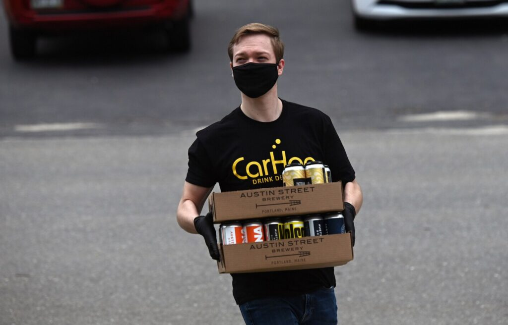 Thomas Brems of Carhop makes a beer delivery in mid-May. Beer delivery, and curbside pickup, are proving highly popular during the pandemic, and many breweries say they plan to continue these services even when breweries are allowed to reopen.