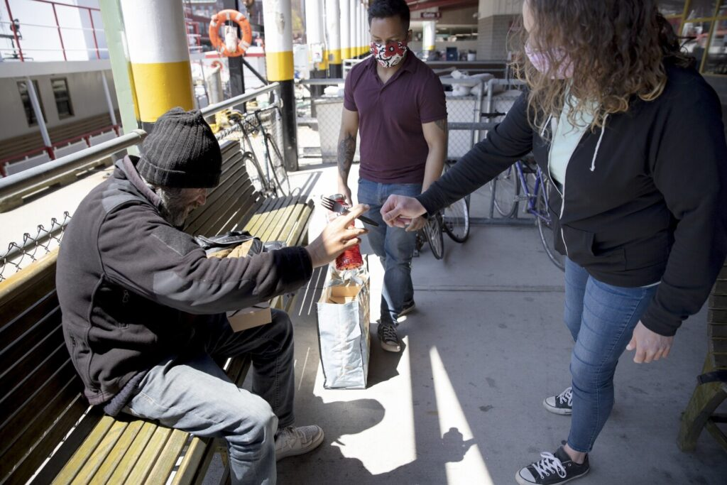 Katie Junkert of The Opportunity Alliance hands a plastic fork to a homeless man at the Maine State Pier in Portland on May 14. Junkert and Ashish Shrestha of Amistad were giving out free meals as part of the Cooking for Community effort. Cooking for Community is one of the programs that will receive grant money from the John T. Gorman Foundation.