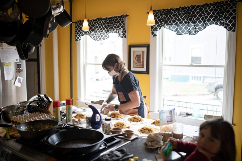 """Erin Abraham makes breakfast burritos Friday in the kitchen of the Chadwick Inn in Portland, where she is the innkeeper. The burritos are sold and donated to Maine Medical Center employees. Abraham says, """"We don't know what the summer will look like. ... I don't know if people will come here, and I don't know if they should."""""""
