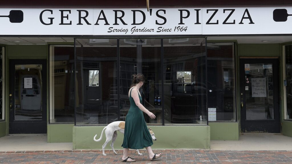 Kelly Flanagan walks past Gerard's Pizza on Water Street in Gardiner Sunday. A sign on the door said the sandwich shop plans to re-open on Tuesday.
