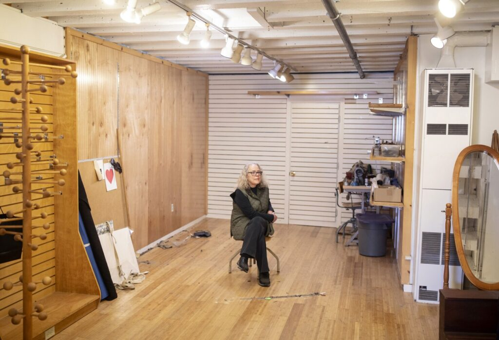 Nancy Lawrence sits in her nearly empty store, Portmanteau, on Wharf Street in the Old Port on Wednesday. Lawrence is closing her shop after over 40 years of selling clothing and accessories, in part because of her fears about the coronavirus.