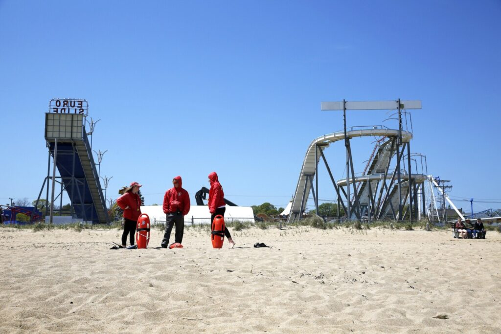 Lifeguards Anna Letourneau, left, Nicholas Czelewicz and Allyson Hickey stand on a relatively quiet Old Orchard Beach in late May. Airbnb rentals have jumped nationally as states, including Maine, open – with restrictions – to tourists.