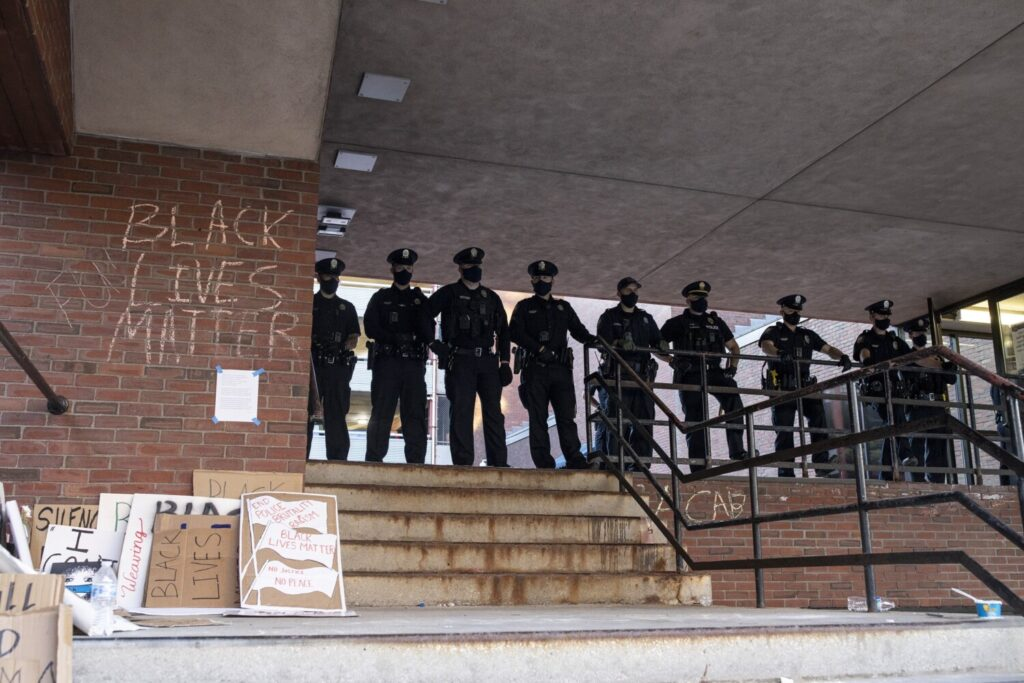 Portland police stand at the top of stairs as protestors disperse outside of the Portland police station on Middle Street on May 31.
