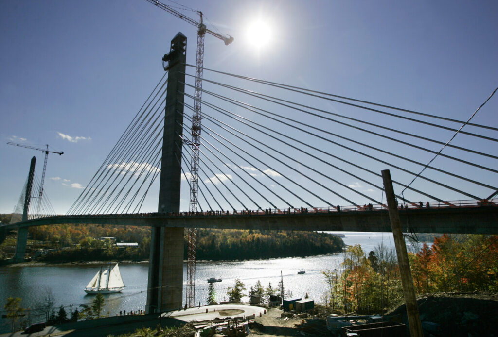A large sailboat leads a boat parade under the Penobscot Narrows Bridge and Observatory, Oct. 14, 2006, during Bridgewalk, a celebration of the newly constructed bridge.