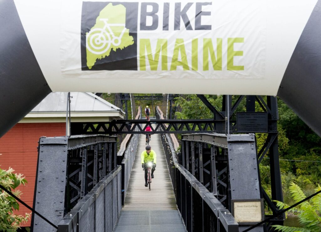 Riders cross the Two Cent Bridge from Winslow as they make it to Head of Falls in Waterville to finish the 2019 BikeMaine weeklong cycling trip around the state. Some 450 riders participate in the annual event.