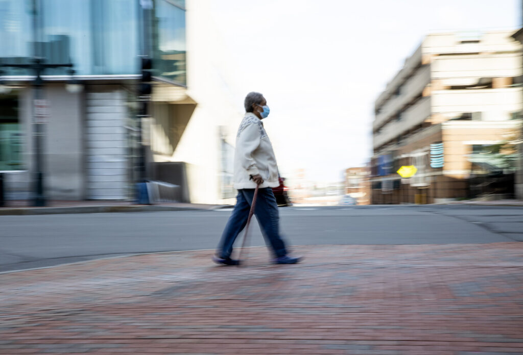 A woman walks on a largely deserted Congress Street in Portland on Monday morning.
