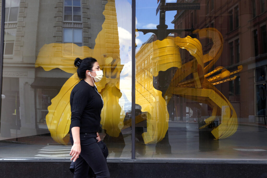 A woman wears a mask while walking past the Maine College of Art in Portland on Saturday.