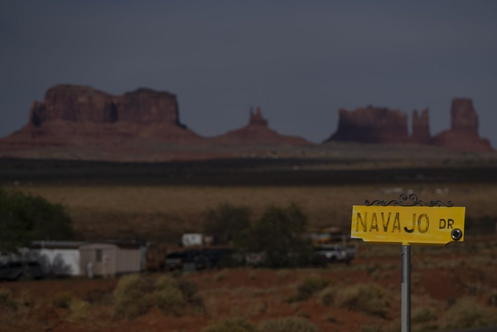 Sentinel Mesa, homes and other structures in Oljato-Monument Valley, Utah, on the Navajo Reservation, stand in the distance. Even before the pandemic, people living in rural communities and on reservations were among the toughest groups to count in the 2020 census.
