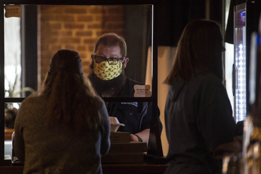 A patron at Portland Pie pays for his to-go order in Waterville on Friday, the day Gov. Janet Mills ordered residents to wear masks in public places where physical distancing is difficult to maintain to prevent the spread of COVID-19.