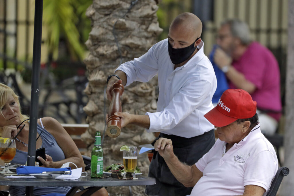 A food server wearing a protective face mask waits on customers Monday at the Parkshore Grill restaurant in St. Petersburg, Fla. Several Florida restaurants are reopening at 25 percent capacity as part of  Gov. Ron DeSantis' plan to stop the spread of the coronavirus.