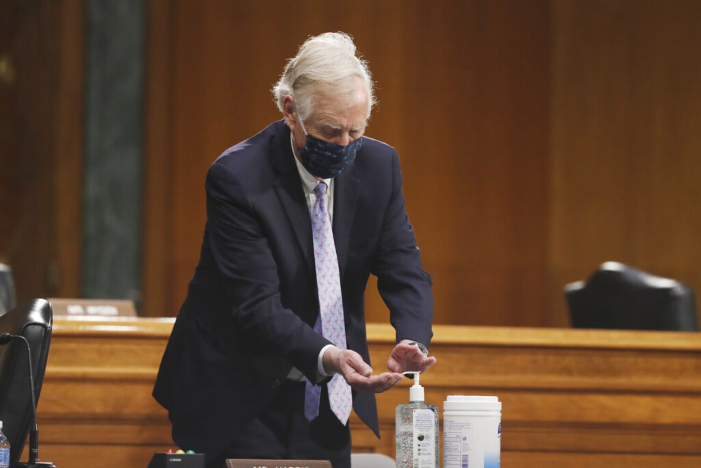 Sen. Angus King, I-Maine, uses hand sanitizer during a Senate Intelligence Committee nomination hearing for Rep. John Ratcliffe, R-Texas, on Capitol Hill in Washington on Tuesday. The panel is considering Ratcliffe's nomination for director of national intelligence.