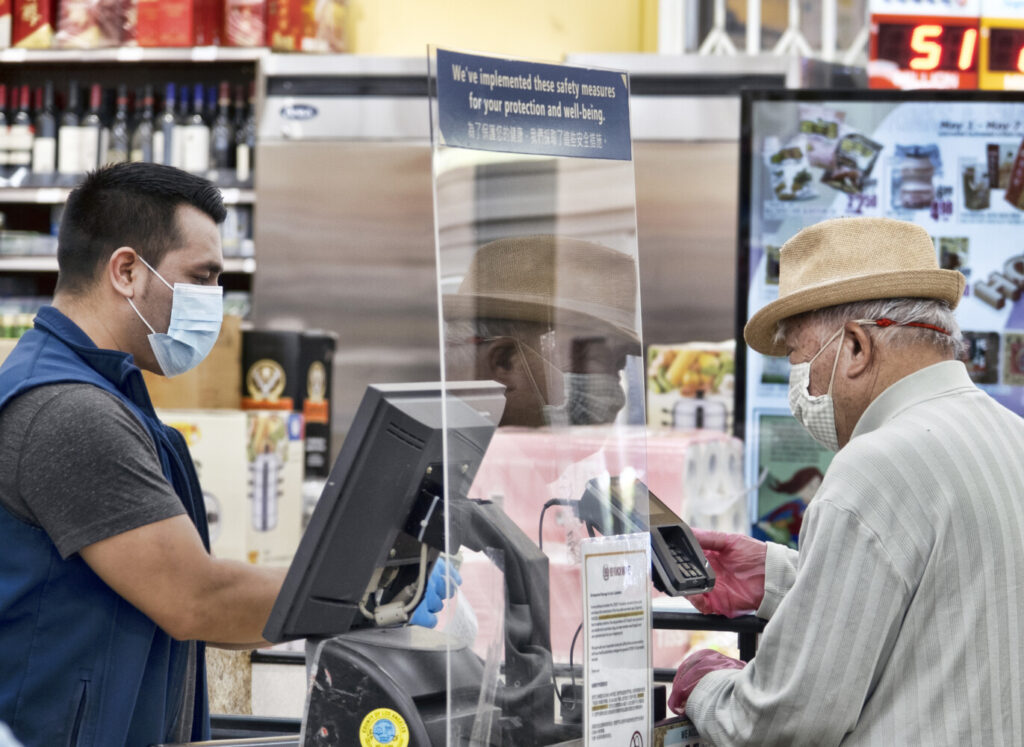 A grocery worker, wearing a protective mask and gloves, helps check out a customer  at the 99 Ranch Market on Tuesday in Los Angeles.