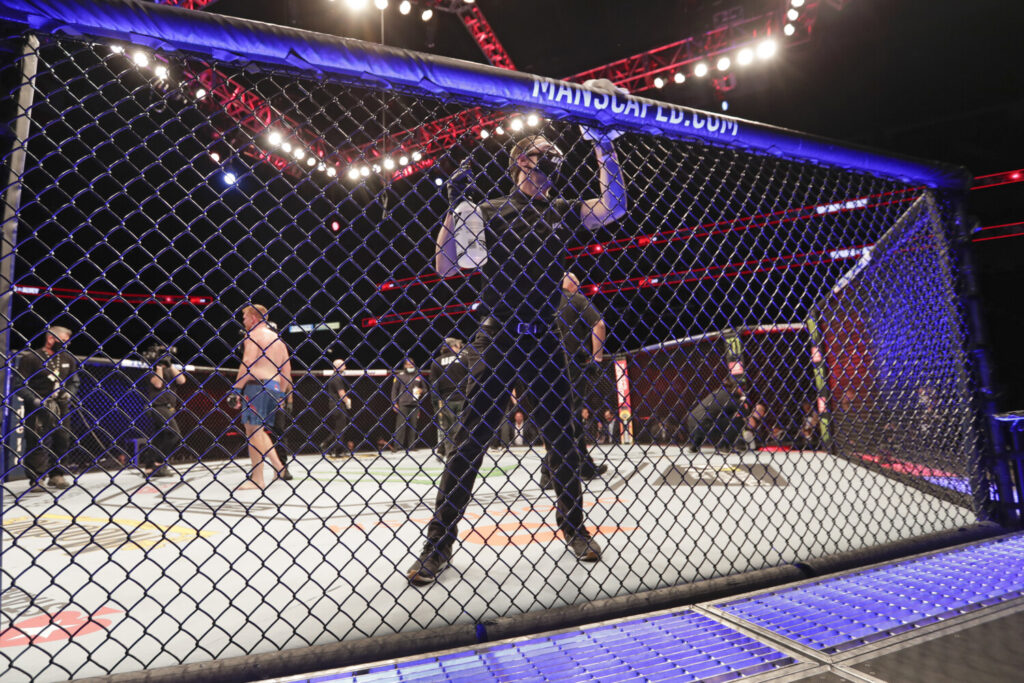 A worker wipes down the octagon between bouts during UFC 249 on Saturday in Jacksonville, Florida.