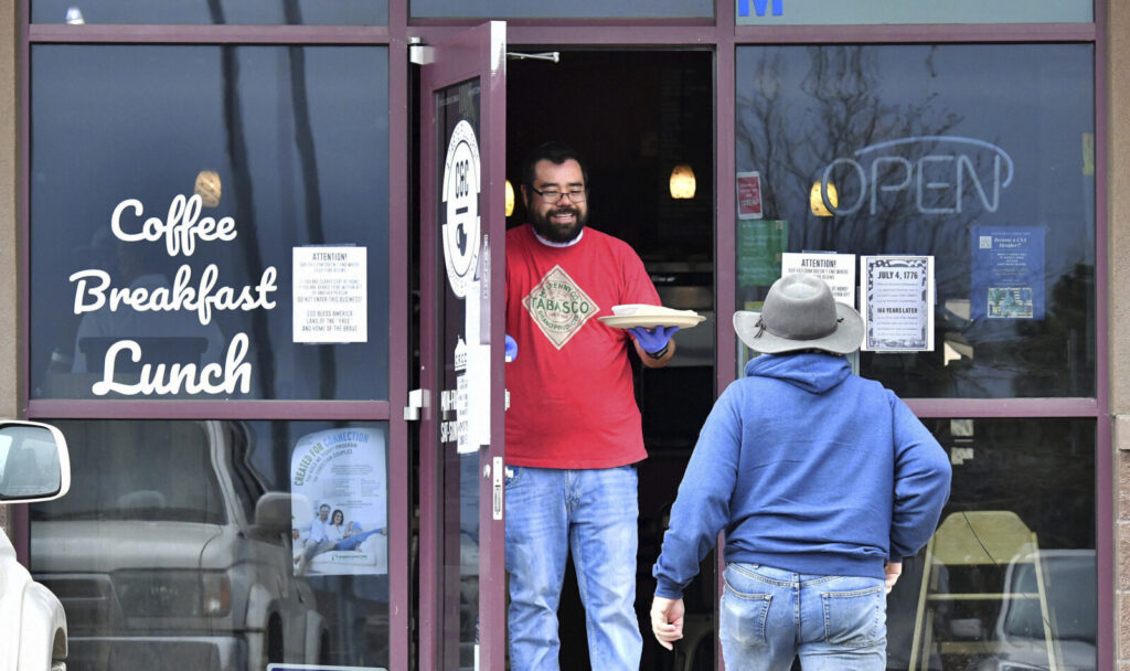 Jesse Arellano hands a breakfast burrito to his friend and regular, Robert Taylor, from the front door of his restaurant, C&C Breakfast and Korean Kitchen, in Castle Rock, Colo., on Monday. Arellano and his wife, April Arellano, opened their restaurant for Mother's Day and had a packed restaurant at times Sunday. When video from the scene went viral, the Arellanos received both backlash and support. The restaurant was ordered to close Monday and had its license suspended indefinitely by health officials.