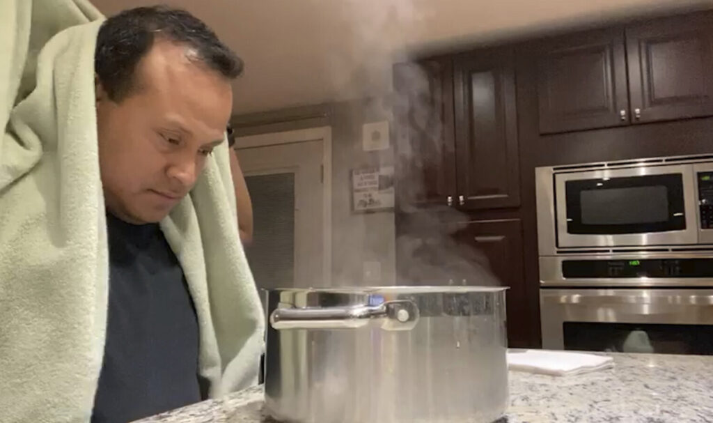 Alex Melo uses a steaming pot for a nebulizing treatment at his home in York, Maine. The retired Marine became critically ill with COVID-19 in April and spent a few days on a ventilator for pneumonia. He also developed blood clots that threatened his heart and lungs.