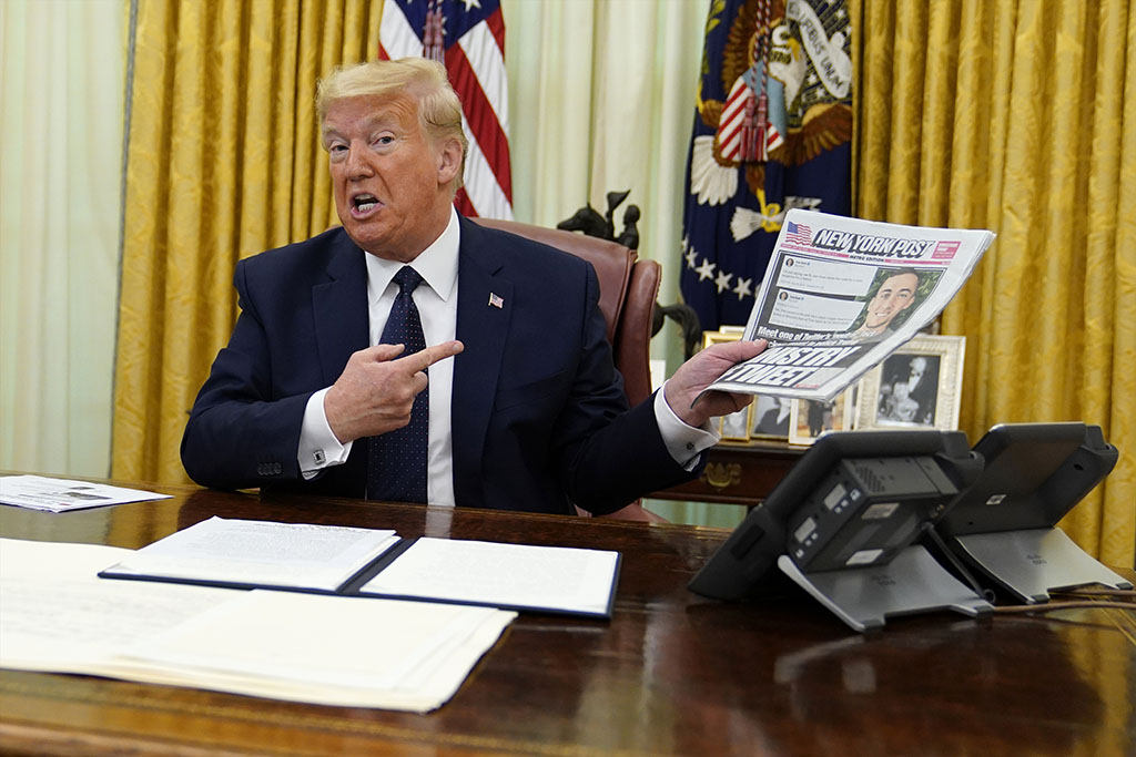 President Trump holds up a copy of the New York Post as speaks before signing an executive order Thursday aimed at curbing protections for social media giants.