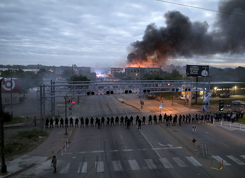 Law enforcement officers amassed in Minneapolis early Friday as fires burned after a night of protests of the death of George Floyd. Floyd died after being restrained by Minneapolis police officers on Memorial Day.