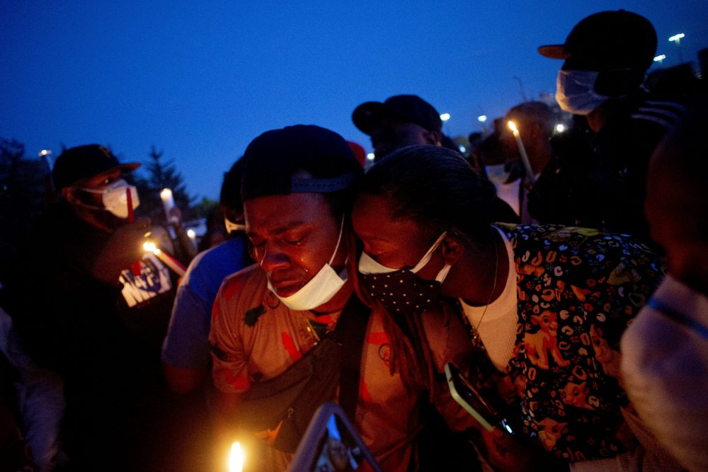 Maalik Mitchell, center left, sheds tears as he says goodbye to his father, Calvin Munerlyn, during a vigil Sunday in Flint, Mich. Munerlyn was shot and killed Friday at a Family Dollar store in Flint. He'd worked at the store as a security guard for a little more than a year.